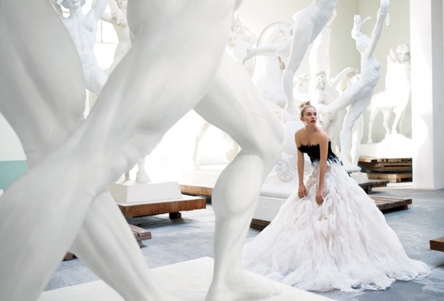 Sienna Miller, by Mario Testino, in a long fethers dress, surrounded by statues