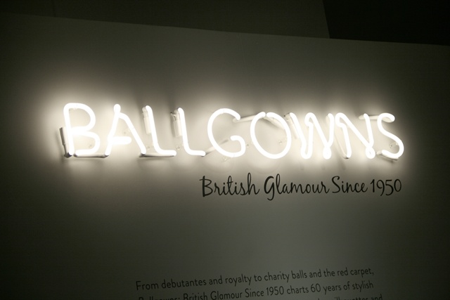 """A neon light with """"Ballgowns"""" written on a wall of the museum"""