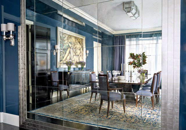 Victoria Hagan Interiors used an antique buffet and chairs in this design reflected in an expansive mirror.