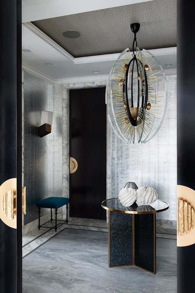 The desirable design of this entryway begins with the black and gold doors. A petite entryway table and stool, along with a bold chandelier, complete the design.