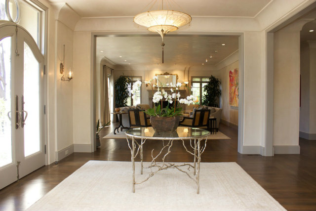 This entryway design by Juli Baier Interior Design makes use of the large foyer by adding a decorative center table at the entrance, complemented by a unique chandelier.