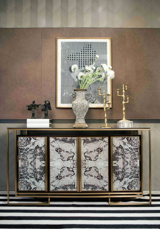 Starting off our impressionable entryways is this attractive entrance that mixes black and white patterns and oriental touches throughout the design. The striking storage cabinet definitely makes a statement with the patterned doors and gold touches.
