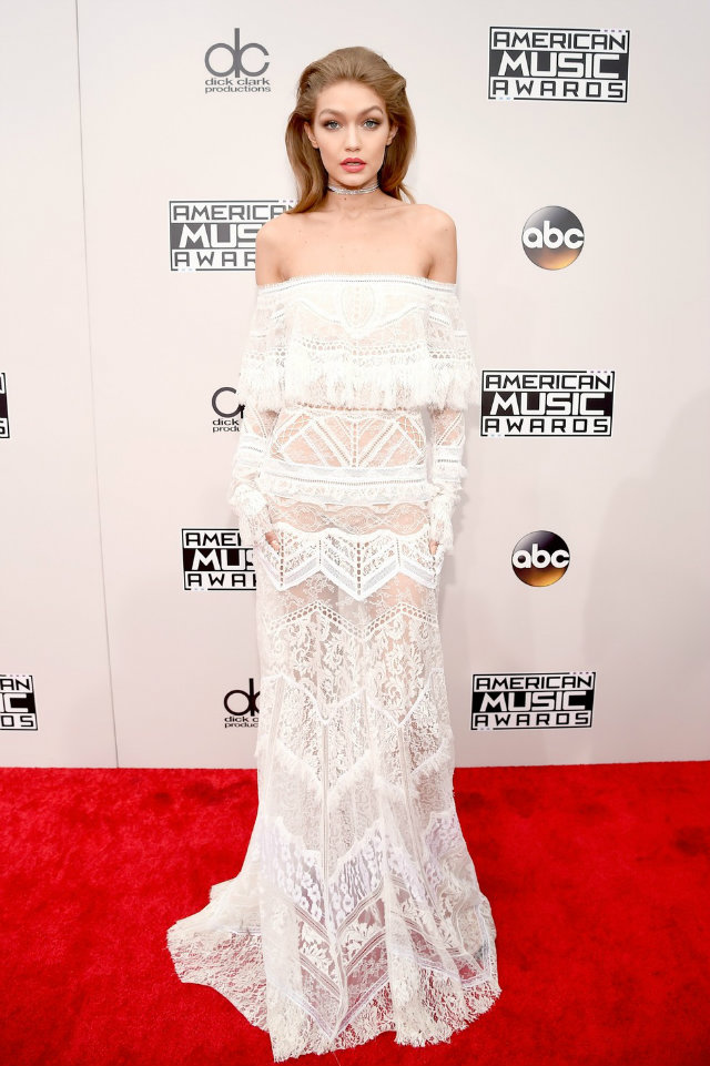 The American Music Awards host, Gigi Hadid, walked the red carpet in a white lace off-the-shoulder Roberto Cavalli gown.