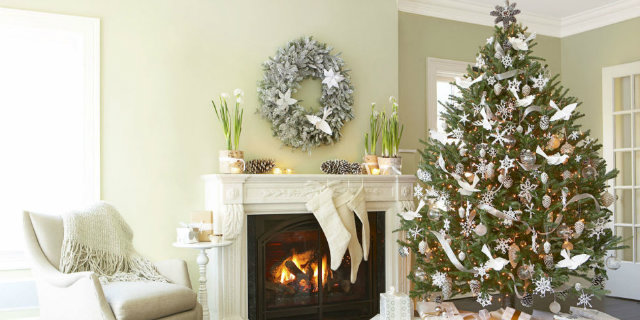 This scene depicts a neutral Christmas wonderland with a lot of crisp white. The Christmas tree channel's the room's monochrome look with white paper doves, frosted pinecones and white ornaments.