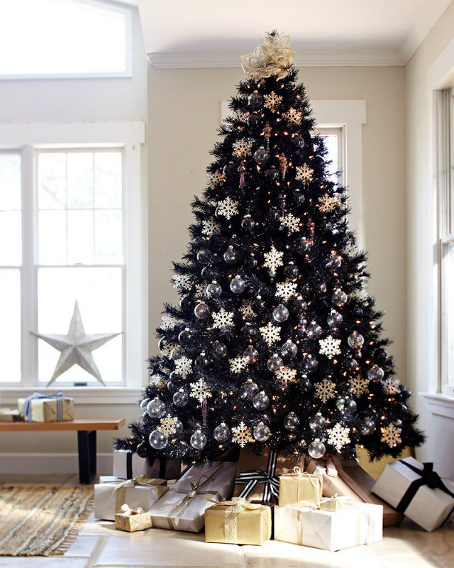On the other hand, a black tree evokes luxury and sophistication like this jaw-dropping black Christmas tree decorated with glittering snowflakes and ornaments. A pile of matching gold, white and black presents underneath is a welcoming touch.