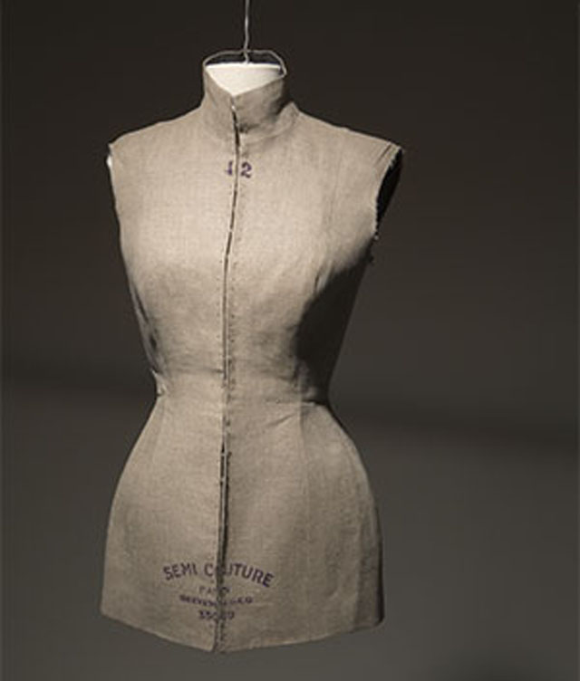"12 Fashion Exhibitions to Visit in 2017: The Body: Fashion and Physique - Sleeveless dress form tunic/jacket of beige linen moulded after standardized dress form, with high band collar, hook and eye CF closure from neckline to hem, and printed with ""42"" at neck, and ""SEMI COUTURE/PARIS/BREVETE.S.G.E.G. 35059"" at hem fashion exhibition 12 Fashion Exhibitions to Visit in 2017 ue 2008"