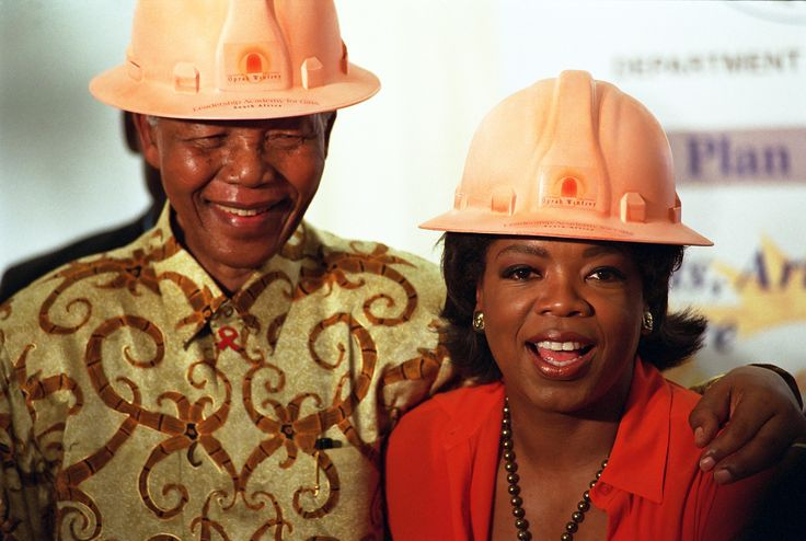 "Women Empowerment - 06 Dec 2002, Henley On Klip, Gauteng Province, South Africa --- Nelson Mandela has his arm around the shoulders of author and talk show host Oprah Winfrey after they don construction hard hats to break the ground for her $10 million Leadership Academy for Girls in South Africa. She described Mandela as her ""hero"" and he called her a ""queen."" --- Photo by Louise Gubb/ Corbis SABA --- Image by © Louise Gubb/Corbis"