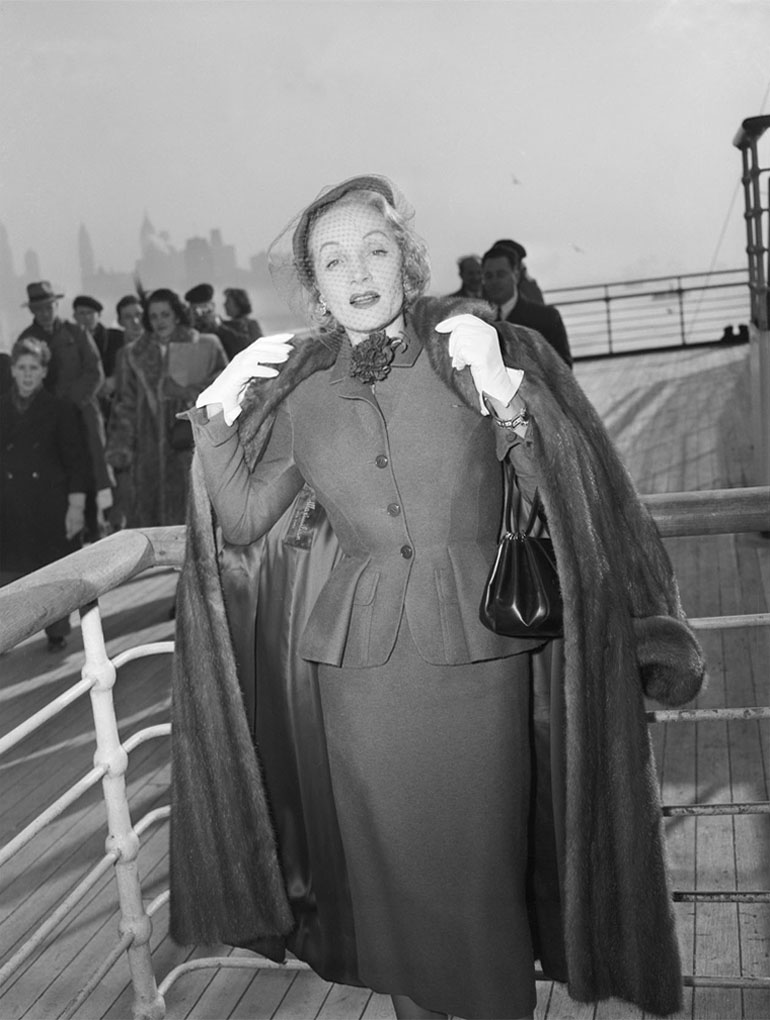 Marlene Dietrich wearing a day suit by Christian Dior onboard the Queen Mary, arriving in New York, 21 December 1950 © Getty Images - Peabody Essex Museum