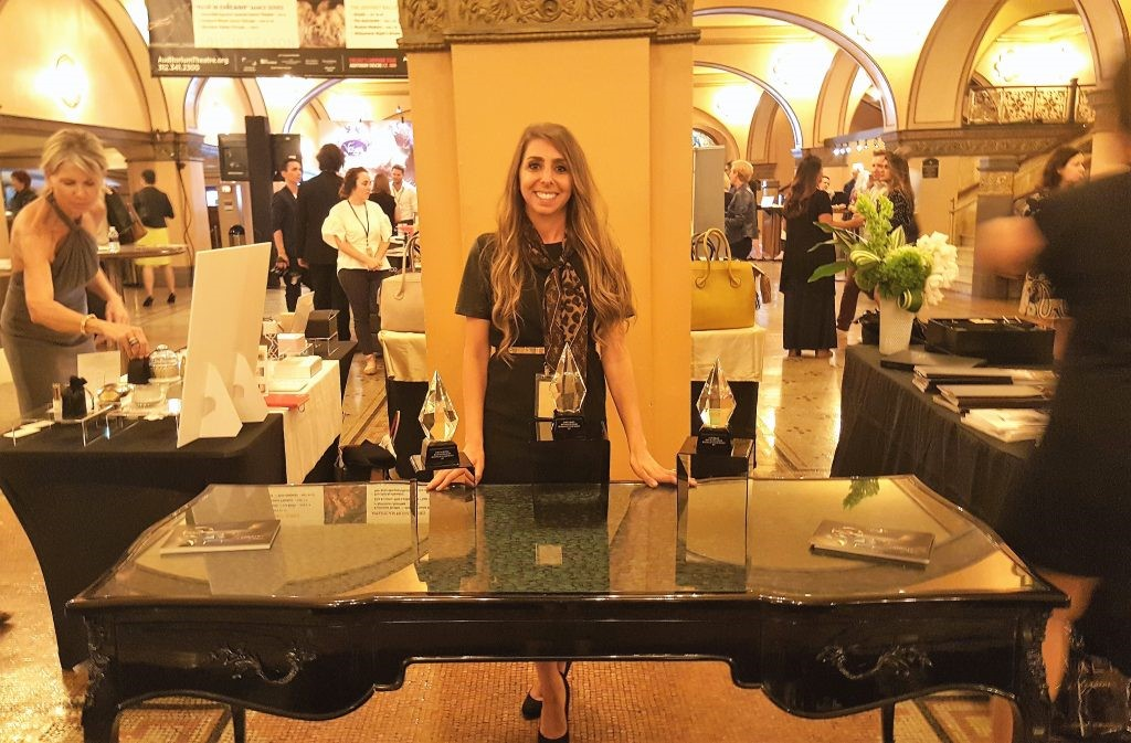 Press and Public Relations Associate, Natalia, at the KOKET booth in the golden lobby at BOLD. Photography by Deborah Main. Sexy chair - black lacquer desk by koket - peacock feather top desk - ormolu desk - exotic desk