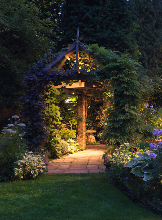 Outdoor decoration ideas - garden arches - garden lighting - Garden lit at night. Wooden pergola clad in vine, clematis and wisteria leads to staddle stone. In beds, hosta, phlox, hardy geranium and box. Boxwood House. Photo by Nicola Stocken