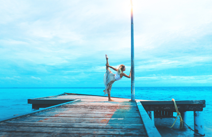 How to Change Your Life - 7 Day Yoga Experiment - Photo by Marvin Meyer on Unsplash - yoga on a dock - beautiful woman doing yoga - yoga at the ocean - fashion yoga