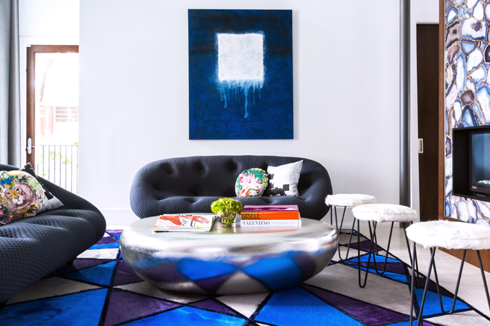 living room by contour interior design with a silver stone shape coffee table and graphic art