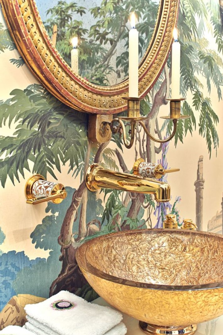 photograph of a powder room with decorative wallpaper, a gold oval mirror, a real candle sconce and a bronze glass bowl sink, visual storytelling by marco joe fazio