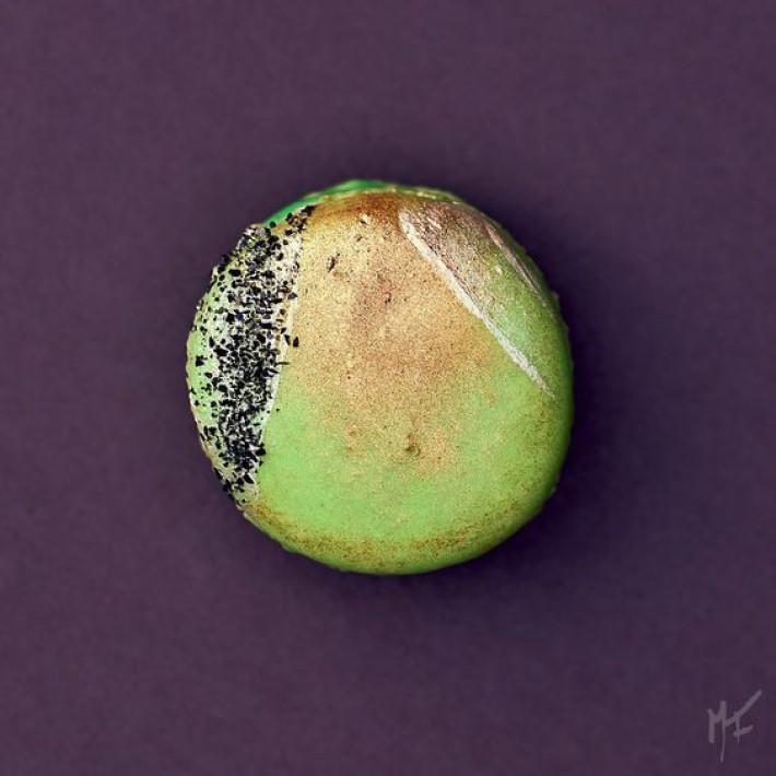 photograph of a green and gold macaroon on a purple background, visual storytelling by marco joe fazio