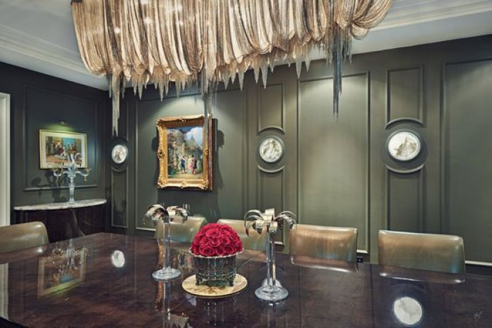 photograph of a dining room with olive green walls and a dripping chain chandelier, visual storytelling by marco joe fazio