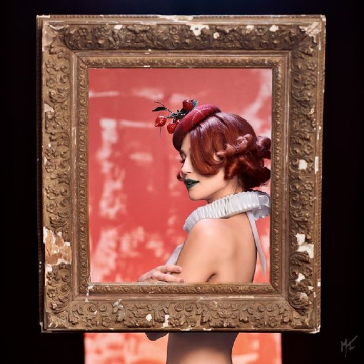 beautiful woman with short red hair wearing a hat and tudor ruff posing in a carved picture frame, visual storytelling by marco joe fazio