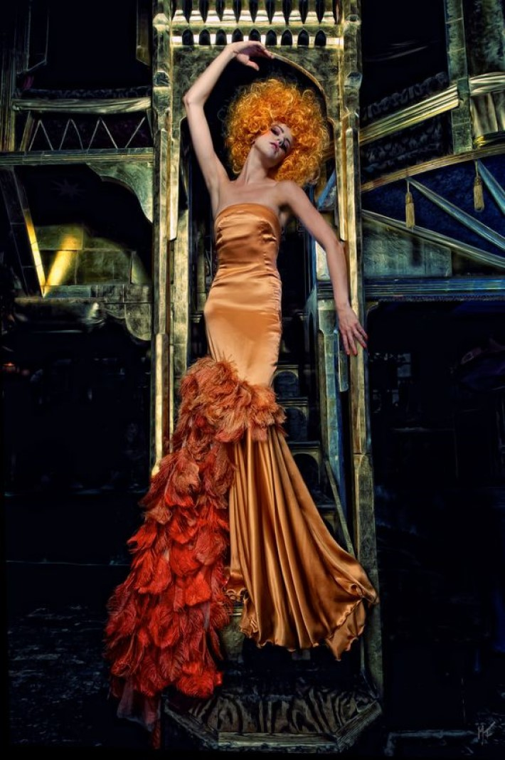 Beautiful women in an orange silk gown with orange curly hair posing in a gold architectural setting, visual storytelling by marco joe fazio