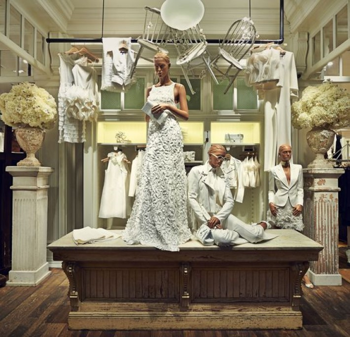 a white retail store setting with mannequins dressed in all white and white chairs hanging from the ceiling, visual storytelling by marco joe fazio