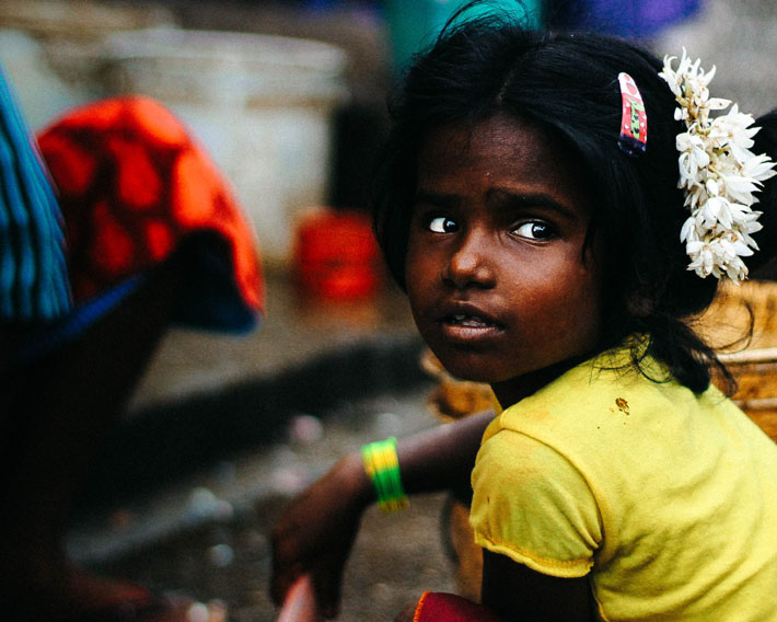 International Day of the Girl Child: Celebrating Girl Power & The Launch of the Obama Foundation's Global Girls Alliance - Photo by Aman Bhargava on Unsplash - Young girl in a yellow shirt with flowers in her hair