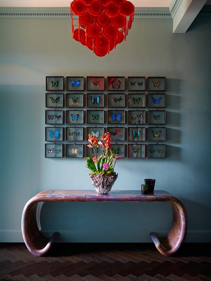 Luxury interior Entryway Design with Butterflies Art, Red Glass Chandelier and Contemporary Console Table by Trilbey Gordon