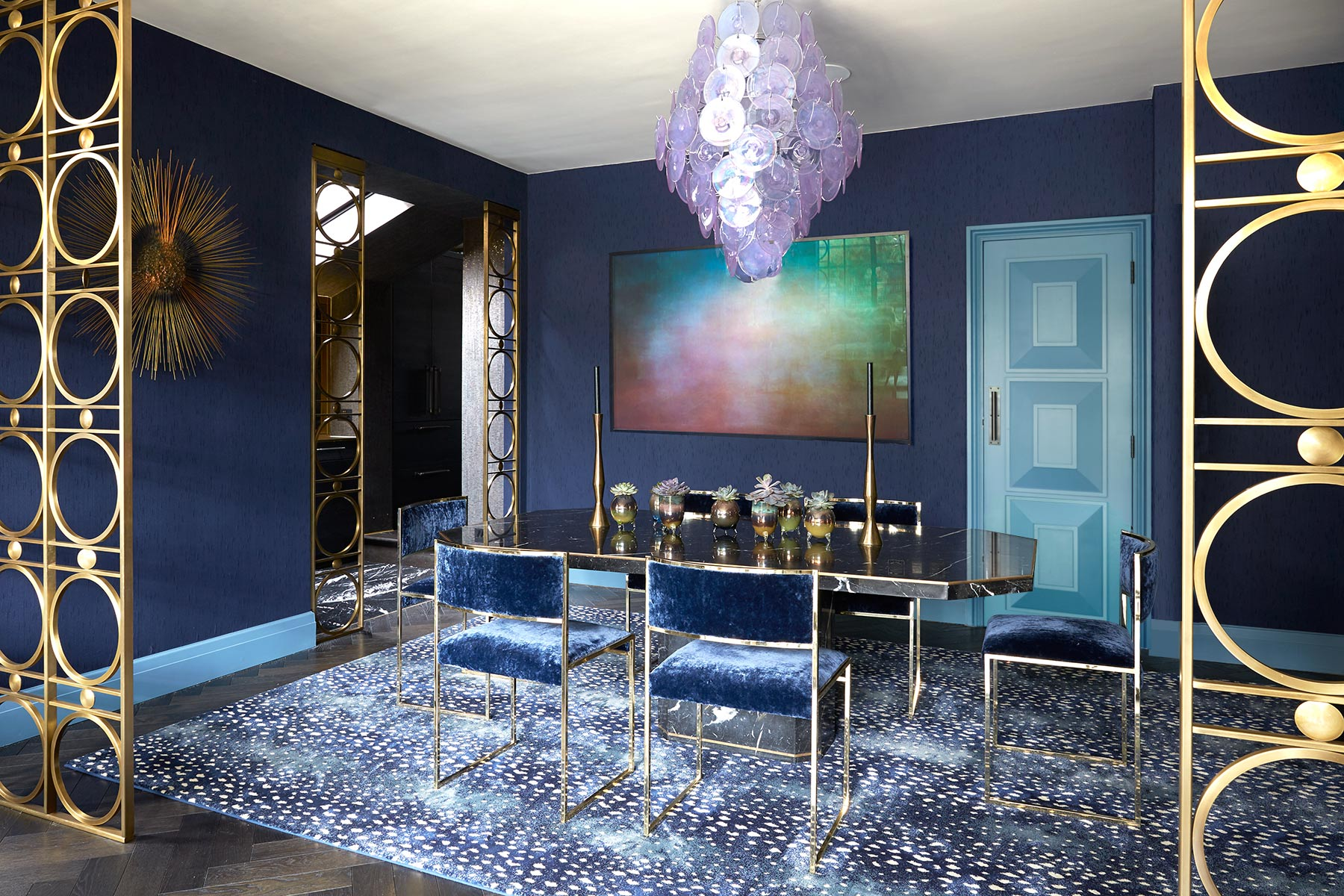 luxury interior Glamorous Blue and Gold Dining Room with Purple Glass Chandelier and Blue Velvet Dining Chairs Designed by Trilbey Gordon
