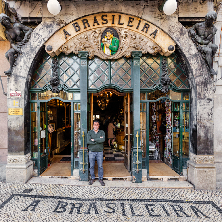 A photograph of the facade of Cafe A Brasileira with owner outside for Lisbon Re-Tale project by Sebastian Erras