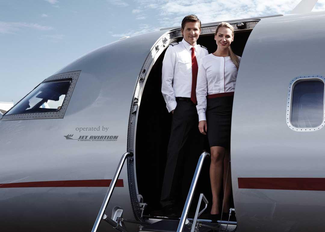 flight attendants standing at the door of a private jet by vistajet