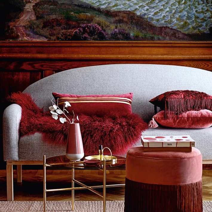 A room with a Grey sofa with red accent pillows and a red fur throw, a red pouf stool with tassel trim and a gold cocktail table - Room Colors and Moods - red psychology