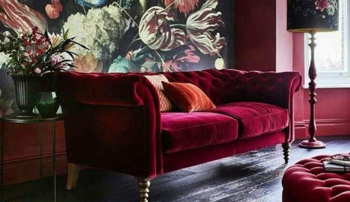 a red velvet tufted sofa against a floral wallpaper - room colors and moods - red psychology - color psychology