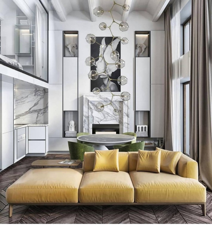 Apartment main room with large contemporary chandelier made of glass balls, a yellow sectional sofa, and a dining table with green dining chairs behind it and a glass wall showing a loft bedroom above the kitchen - room colors and moods - yellow psychology