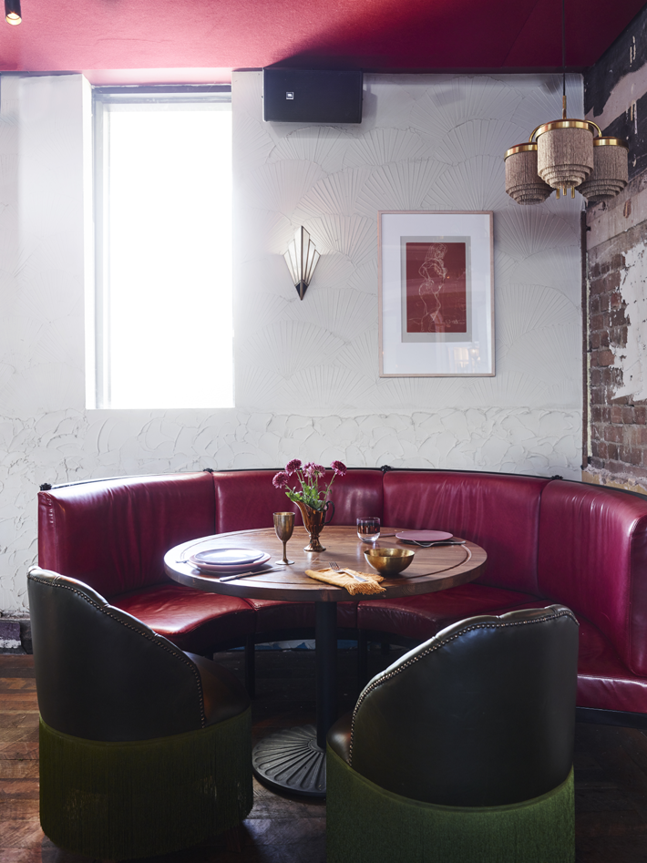 A purple upholstered booth table with an exposed brick wall at the Imperial Hotel Erskineville Sydney Australia - a LGBTQIA+ hotel