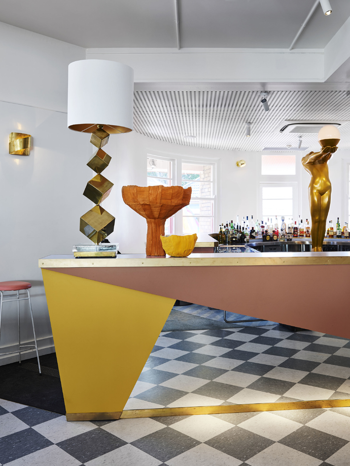 Sculptural gold table lamp on an art deco contemporary yellow, soft pink and mirrored bar at Imperial Up Pizzaeria at the Imperial Hotel Erskineville - Proudly LGBTQIA+