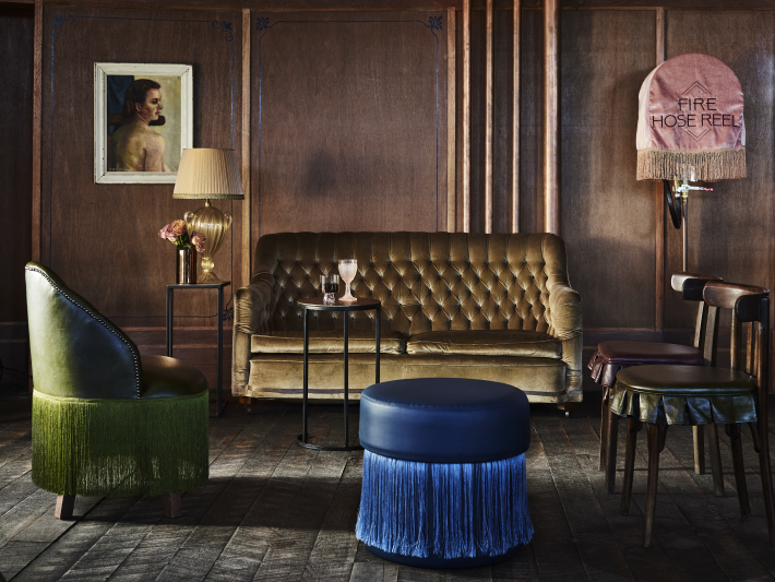 Sitting area with a gold tufted sofa, a green fringed chair and blue fringed ottoman at the Imperial Hotel Erskineville Sydney Australia - a LGBTQIA+ hotel