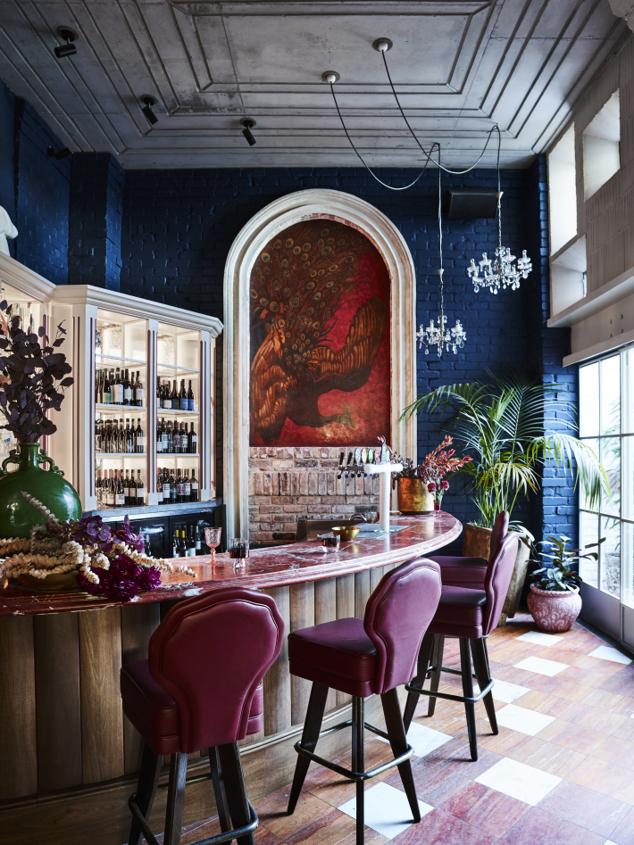 A bar area with blue walls and purple bar stools at the Imperial Hotel Erskineville Sydney Australia - a LGBTQIA+ hotel