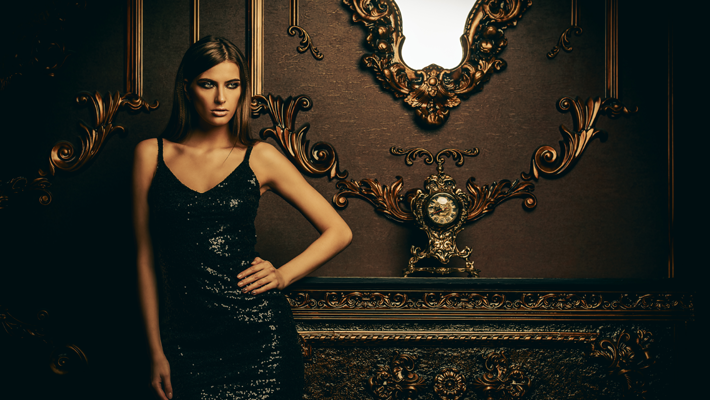 A sexy woman in a black dress standing in front of a highly ornamented gold wall showing this season's must have - confidence