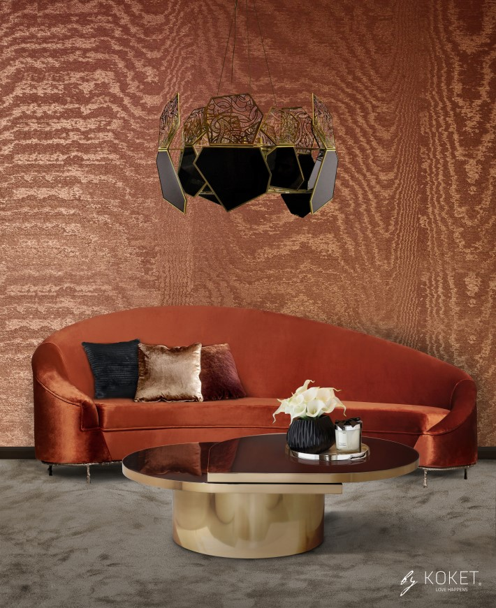 A room with orange moire wallpaper, an orange curved sofa by koket, and a tears koktail table by koket with a black and gold chandelier hypntocic by koket - room colors and moods - orange psychology