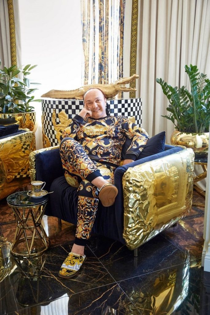 gia eradze sitting in a golden chair by boca do lobo in his luxury interior designed by mironova design