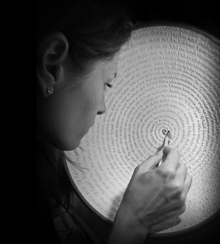 Esma Dereboy working on her ceramic art, a white circle covered with etched words in turkish