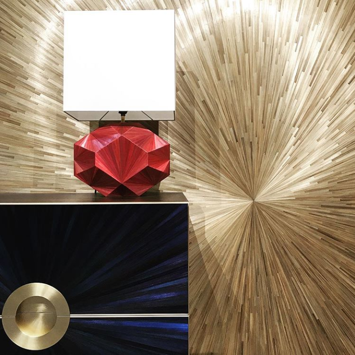 straw marquetry finishes on the wall, a red table lamp and a blue chest of drawers by jallu ebenistes at maison et objet 2019