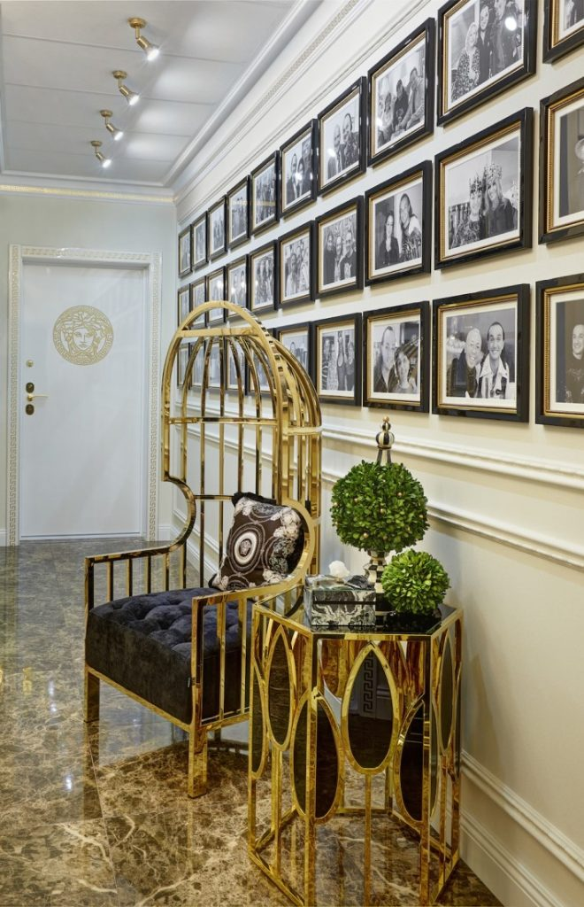 a luxury interior view of the luxurious hallway with a gold chair and side table by Eichholtz in gia eradze's apartment designed by mironova design
