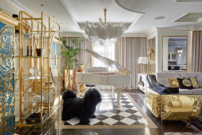 a luxury interior view of the opulent living room featuring a white piano, feather chandelier and mademoiselle armoire by koket in the apartment of gia eradze designed by mironova design
