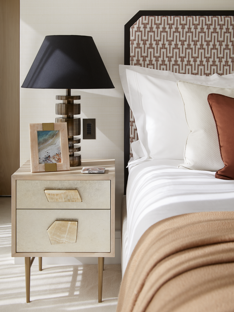 A cream nightstand with stone handles and a bronze bed in a Playful Interior by Elycion