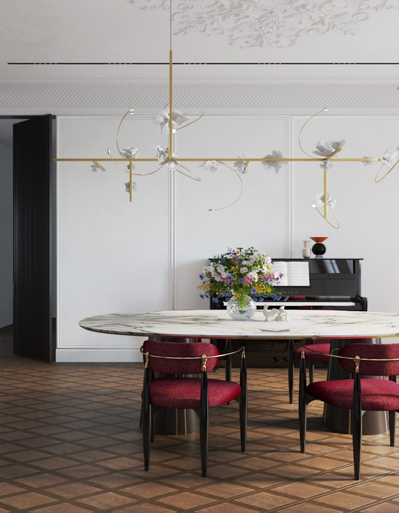 dining room design by Vadim Maltsev with an oval marble dining table, a brass and floral chandelier by pelle and red nahema dining chairs by koket
