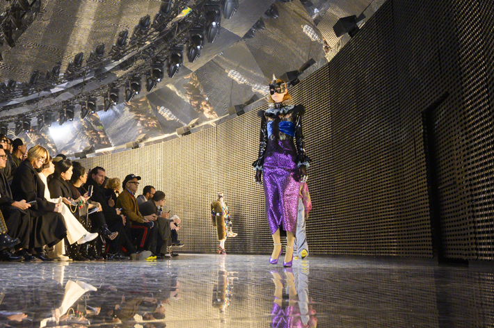 model wearing a purple sparkly skirt and futuristic black top with a spiked collar and black mask walked the runway at the gucci show milan fashion week fall 2019