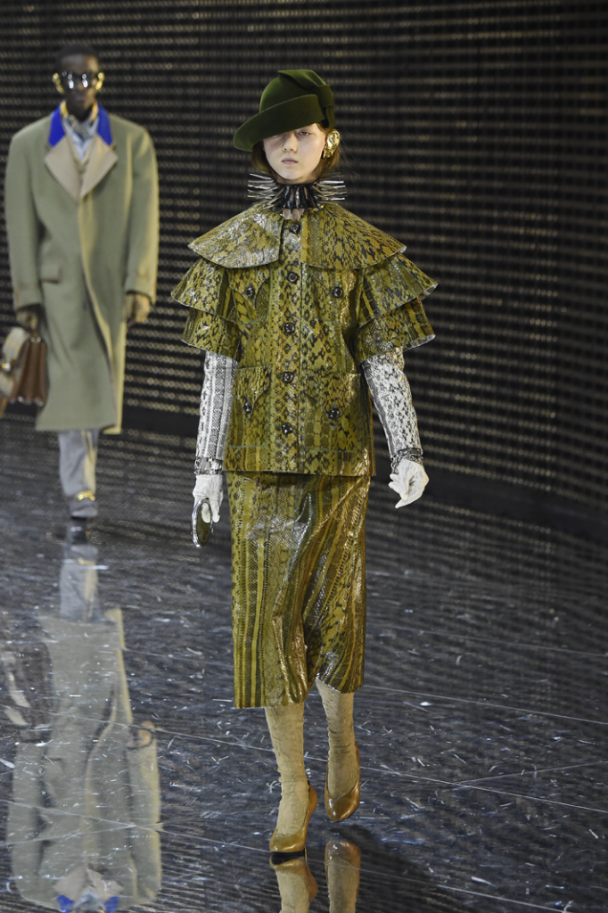 model wearing a green animal print coat and skirt with a spiked collar and large gold metal piece covering her ear walked the runway at the gucci show milan fashion week fall 2019