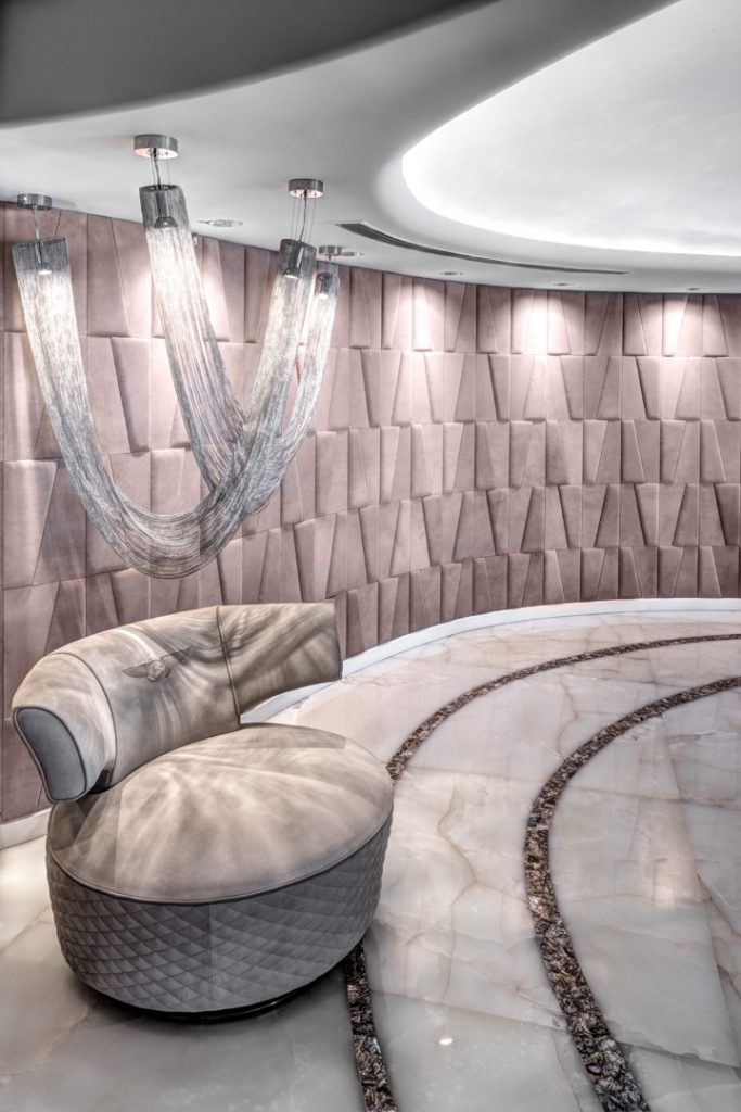 a luxury interior with a curved wall covered in mauve geometric 3d upholstery, a large sculptural chandelier made with silver chain and a Bentley upholstered chair