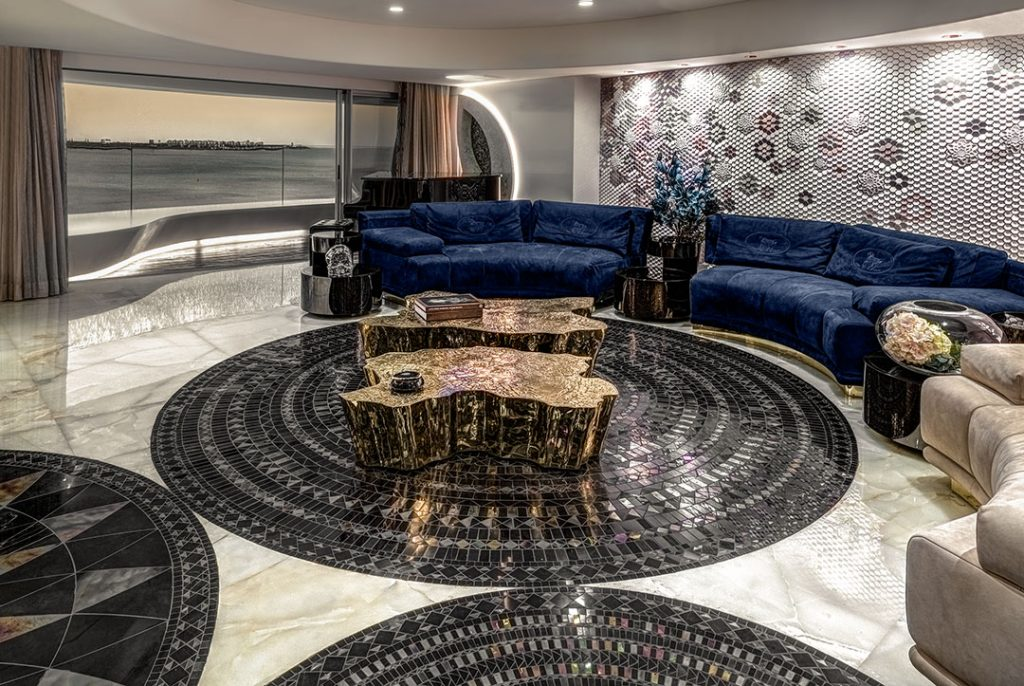 luxury living room design by zz architects featuring a royal blue curved sofa and a black and white marble mosaic floor