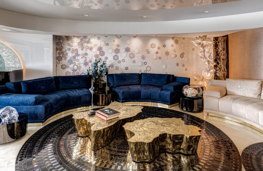 luxury living room design by zz architects featuring a royal blue curved sofa and gold stump-like cocktail tables
