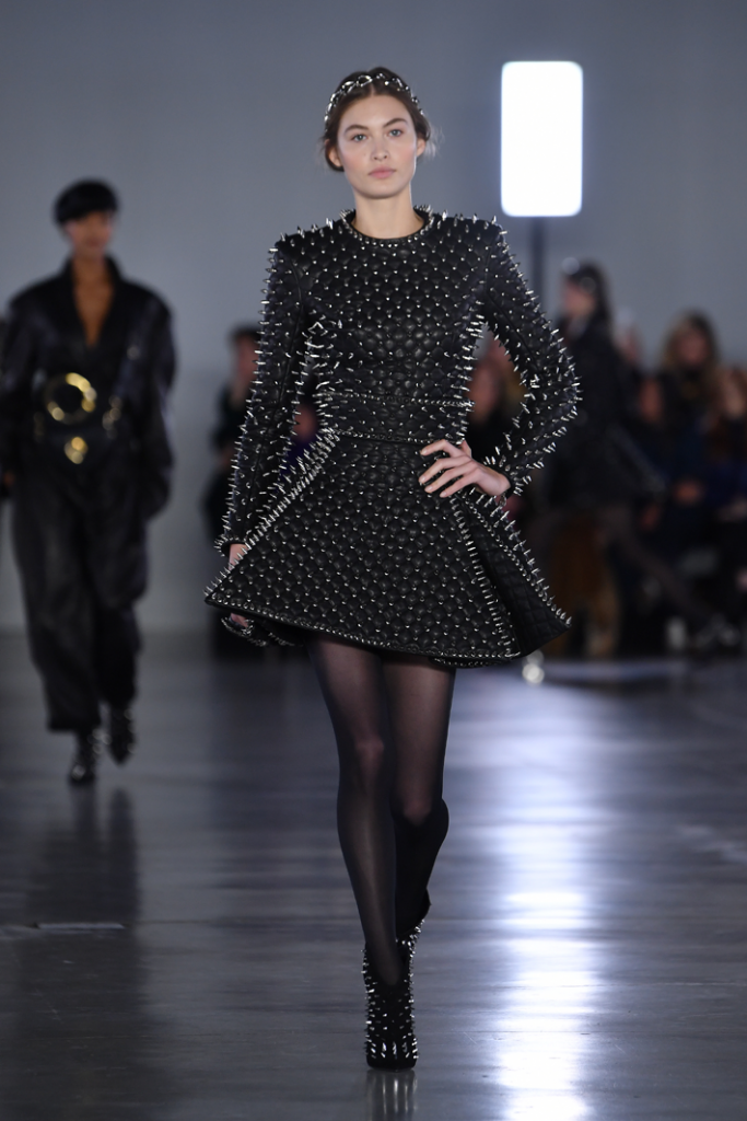 A model walks the runway in a black dress with silver spikes covering it during the Balmain show at Paris Fashion Week Fall/Winter 2019/2020 Womenswear presentation