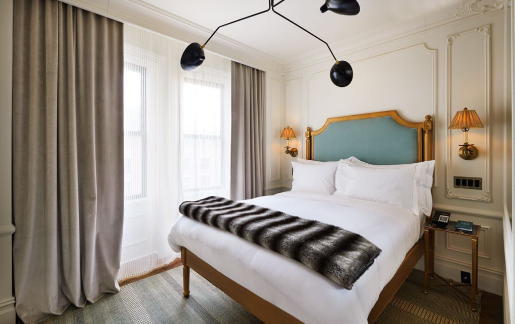 a guest suite at the marlton hotel new york with a fur throw and a teal headboard bed - a top boutique hotel in nyc